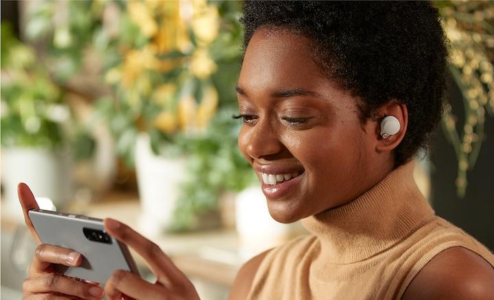 ผู้หญิงที่สวมหูฟัง WF-1000XM4 กำลังรับชมเนื้อหาบนสมาร์ทโฟนของเธอ