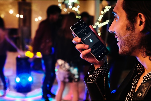 Partygoer using Voice Control via Fiestable app on his smartphone