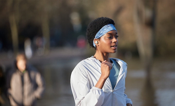ผู้หญิงที่กำลังวิ่งกลางแจ้งโดยสวมหูฟัง WF-1000XM4