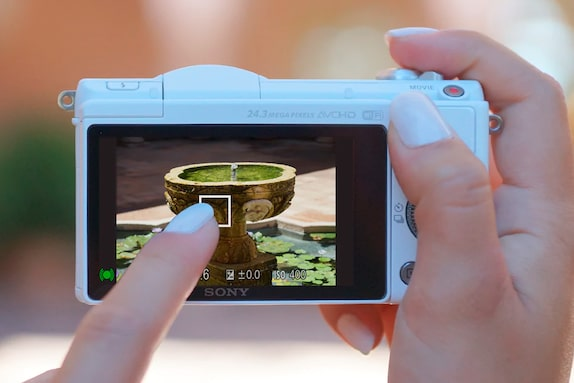 white camera taking picture of a fountain
