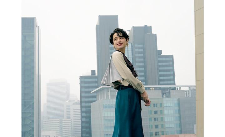 ภาพระยะใกล้ของหญิงสาวบนชั้นดาดฟ้าที่กำลังหันมองผ่านไหล่ของตัวเองแล้วส่งยิ้ม ถ่ายด้วยเลนส์มุมกว้าง 27 มม.